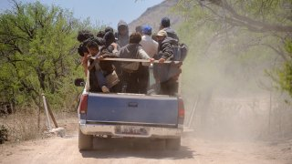 A group of Mexican migrants being transported by Coyotes (people smugglers) to a drop off point in the desert before beginning the treacherous trek through the desert to cross the border into the USA, near the town of Sasabe. Sasabe is the departure point for as many as 1000 migrants a day, most from Mexico, who cross the border illegally into the USA by going around, over, and through the fence between the two countries.
