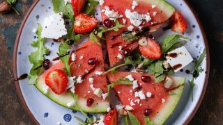 Blue spotted plate with watermelon and strawberry fruit salad with feta cheese, arugula, nuts and balsamic sauce