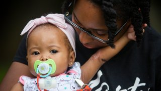 Tyesha Young, who lost her hospital job during the pandemic, holds her baby Jalayah Johnson
