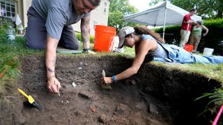 UMass Boston graduate students Nicholas Densley, of Missoula, Mont., left, and Kiara Montes, of Boston, right, use brushes while searching for artifacts at an excavation site, in this Wednesday, June 9, 2021 file photo, on Cole's Hill, in Plymouth, Mass.