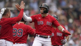 Boston Red Sox's Enrique Hernandez, center, celebrates with teammates after scoring on a sacrifice fly by Xander Bogaerts in the eighth inning of a baseball game against the New York Yankees, Sunday, July 25, 2021, in Boston. The Red Sox won 5-4.