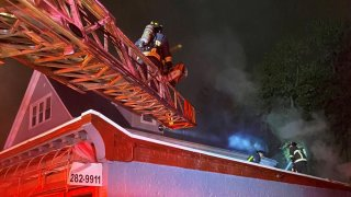 Firemen stand on a crane over a house.