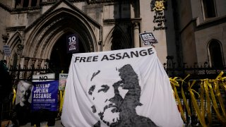 Supporters of WikiLeaks founder Julian Assange hold up a banner as they protest