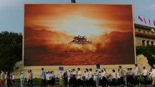 Attendees at a ceremony to mark the 100th anniversary of the founding of the ruling Chinese Communist Party pass by a screen depicting China's Mars spacecraft with its rover landing in Beijing