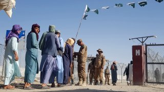 Pakistani soldiers check documents of stranded Afghan nationals returning to Afghanistan at the Pakistan-Afghanistan border crossing point in Chaman on August 14, 2021