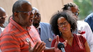 In this June 29, 2021, file photo, Boston Mayor Kim Janey listens as Tito Jackson speaks at a news conference hosted by a coalition of community leaders of black men at City Hall.