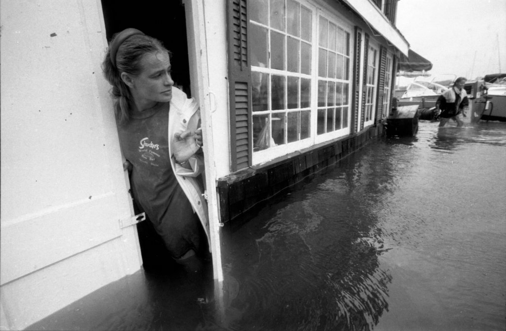 An employee watches Eel Pond flood into Shuckers in Woods Hole, Mass., on Aug. 19, 1991, during Hurricane Bob.