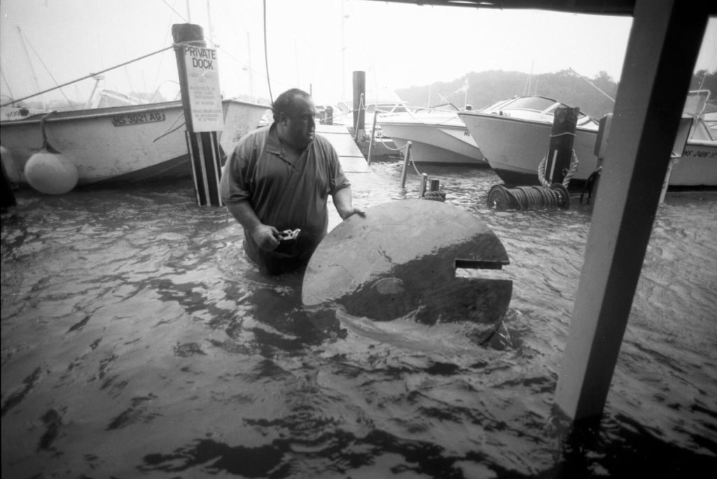 Kevin Murphy, owner of Shuckers Restaurant, tries to save a table as his restaurant floods during Hurricane Bob in Woods Hole, Mass., on Aug. 19, 1991.