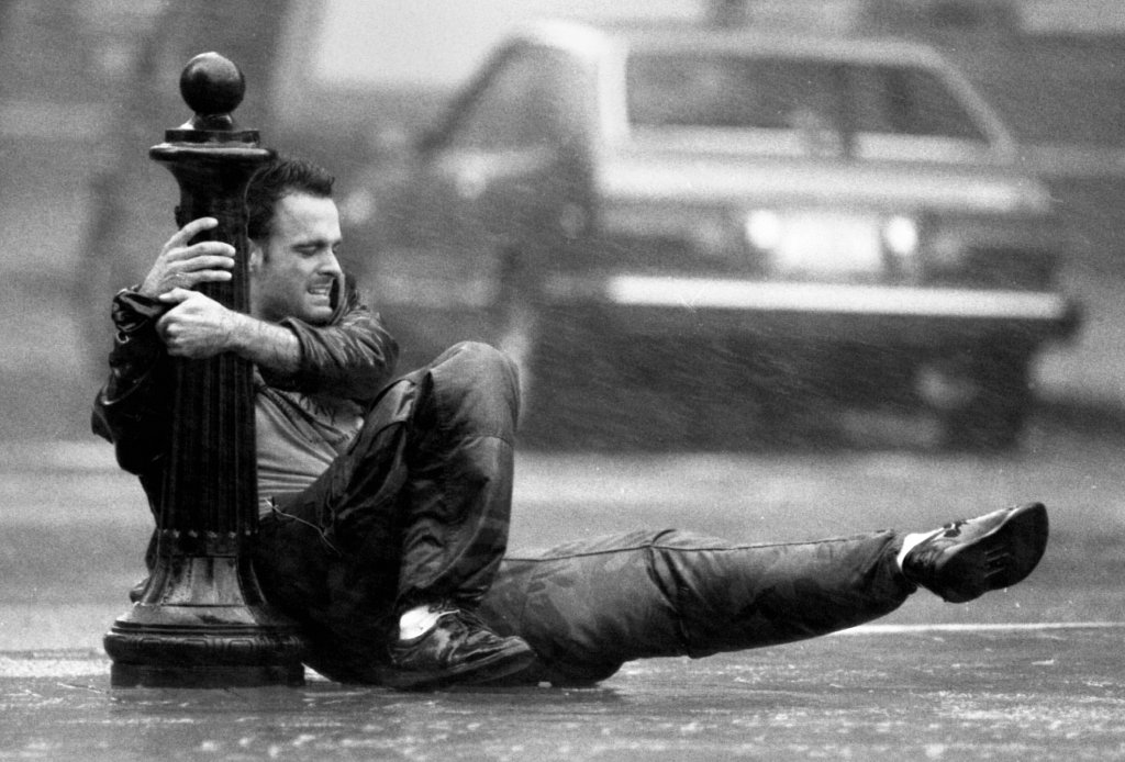A man holds on to a pole in downtown Boston during Hurricane Bob on Aug. 19, 1991.