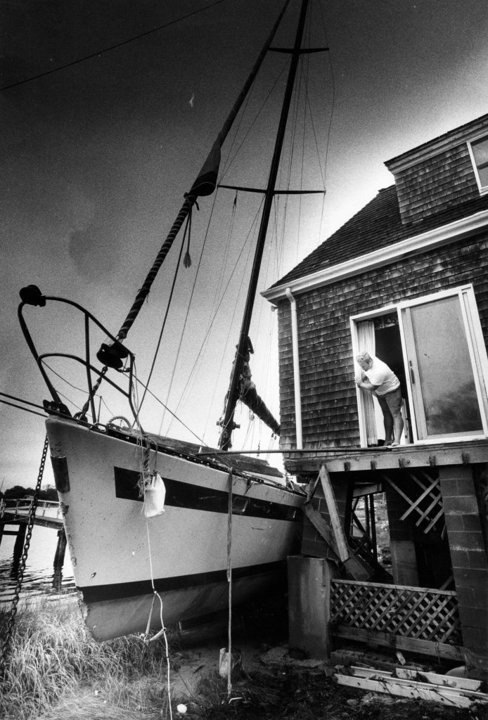Phil Reynolds surveys the damage from a beached sailboat which crashed into his home on Penzance Point in Woods Hole, Mass., on Aug. 20, 1991, after Hurricane Bob.