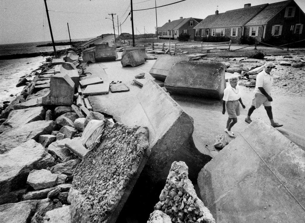 Pieces of a stone wall, each weighing seven tons, that were used to protect Menauhant Road in Falmouth against storm surges were thrown on the road during Hurricane Bob. A couple walks by Aug. 27, 1991.