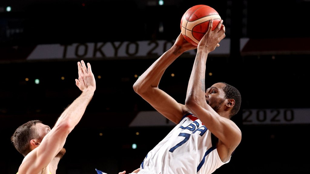 Kevin Durant, in white, fades away with an Australian hand reaching to block his jumper