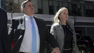 In this April 3, 2019 file photo, investor John Wilson, left, arrives at federal court in Boston with his wife Leslie to face charges in a nationwide college admissions bribery scandal.