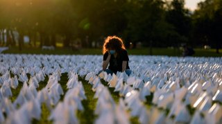 """FILE - In this Sept. 17, 2021, file photo, Zoe Nassimoff, of Argentina, looks at white flags that are part of artist Suzanne Brennan Firstenberg's temporary art installation, """"In America: Remember,"""" in remembrance of Americans who have died of COVID-19, on the National Mall in Washington. Nassimoff's grandparent who lived in Florida died from COVID-19."""
