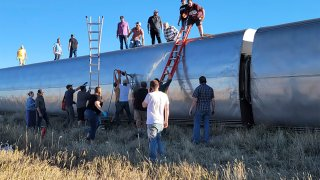 In this photo provided by Kimberly Fossen people work at the scene of an Amtrak train derailment on Saturday, Sept. 25, 2021, in north-central Montana. Multiple people were injured when the train that runs between Seattle and Chicago derailed Saturday, the train agency said.