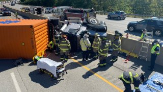Firefighters work to free a driver after a truck crash on the Massachusetts Turnpike