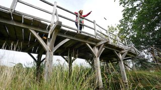 Silke Lohmann of Summers Place Auctions stands on the original Poohsticks Bridge from Ashdown Forest