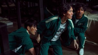 """This undated photo released by Netflix shows South Korean cast members, from left, Park Hae-soo, Lee Jung-jae and Anupam Tripathi in a scene from """"Squid Game."""""""