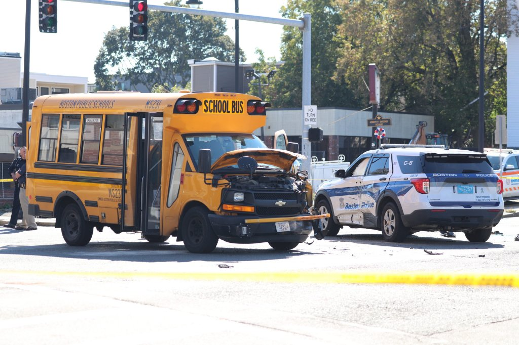 A damaged school bus and Boston police cruiser at the scene of a crash in Dorchester on Friday, Oct. 8, 2021.