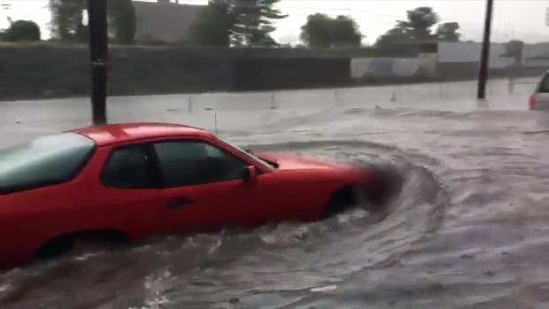 WATCH: Car Tries to Drive Through Flooded Street