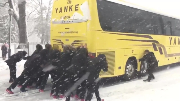 [NATL-NECN] Northeastern Women's BBall Team Pushes Bus During Nor'easter
